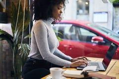 一件灰色夹克的卷曲非裔美国人使用与4G互联网的无线连接 图库摄影