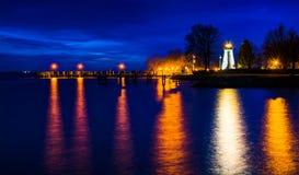 一致点灯塔和一个码头在晚上在格雷斯港 库存图片