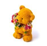 一头熊的橙色小雕象与在白色背景隔绝的花的 免版税库存图片