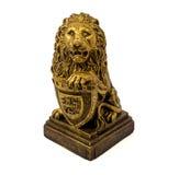 一头狮子的金小雕象与在白色背景隔绝的盾的 免版税库存图片