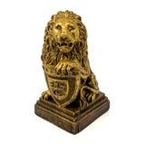 一头狮子的金小雕象与在白色背景隔绝的盾的 免版税图库摄影