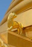 一头狮子的金黄雕象在Wat Bowonniwet Wihan chedi佛教寺庙的基地的1826 曼谷 泰国 免版税库存照片