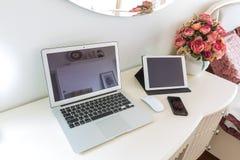 一间现代床屋子的内部有便携式计算机、片剂和巧妙的电话的 库存图片