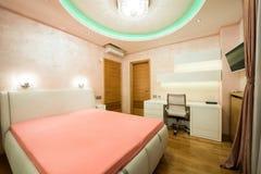 一间现代橙色卧室的内部有豪华五颜六色的天花板的 图库摄影