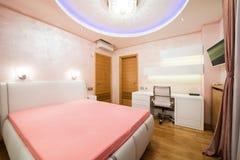 一间现代橙色卧室的内部有豪华五颜六色的天花板的 库存图片