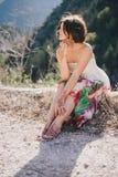 一件现代礼服的年轻美丽的妇女有摆在山中的mehendi的 图库摄影