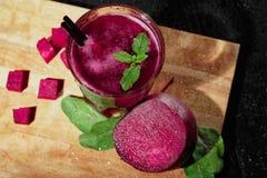 一份甜甜菜饮料的顶视图与秸杆的 桃红色甜菜根立方体和沙拉在木背景 素食者圆滑的人 免版税库存照片
