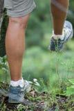 一年轻男性收养的脚用在远足期间的一根远足的棍子由在泥的山决定 图库摄影