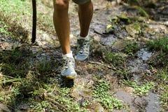 一年轻男性收养的脚用在远足期间的一根远足的棍子由在泥的山决定 免版税库存图片