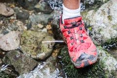 一年轻男性收养的脚用在远足期间的一根远足的棍子由在泥的山决定 库存照片