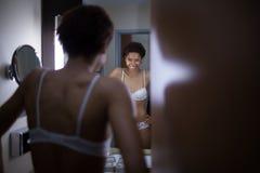 一件白色内衣的年轻黑人美丽的女孩在镜子敬佩自己 免版税库存图片