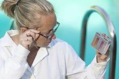 一件白色外套和玻璃的女孩在水池附近观看测试器的检查酸碱度和氯内容在水中 免版税库存图片