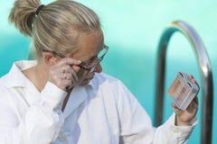 一件白色外套和玻璃的女孩在水池附近观看测试器的检查酸碱度和氯内容在水中 免版税图库摄影