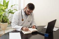 一件白色外套的一位医生输入某事您的日历笔 库存照片