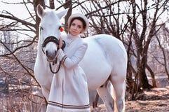 一件白色外套的端庄的妇女 库存照片