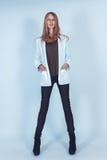 一件白色夹克和长裤的美丽的女孩 库存照片