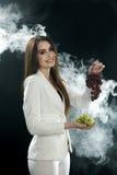 一件白色夹克的一个女孩在她的手和微笑上拿着葡萄在黑背景,报道用抽烟蒸气 库存照片