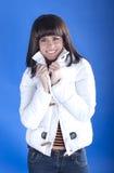 一件白色夹克的妇女在蓝色背景 库存照片