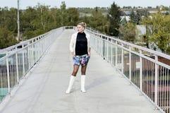 一件白色夹克的性感的妇女和在桥梁的白色起动 免版税库存图片