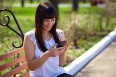 一件白色女衬衫的东方美丽的女孩在公园在电话坐并且写sms,情感 库存图片