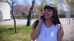 一件白色女衬衫的东部美丽的女孩在公园走微笑和谈话在电话 影视素材