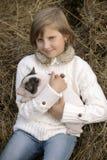 一件白色女衬衫的小女孩坐并且拿着小猪并且微笑 生活方式画象 免版税库存照片