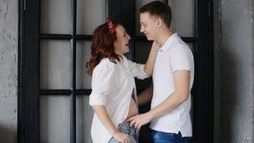 一件白色女衬衫的美丽的孕妇 拥抱她的丈夫,看他在眼睛和微笑 影视素材
