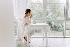 一件白色女衬衫的美丽的浅黑肤色的男人,在明亮的大阳台的饮用的咖啡 免版税库存图片