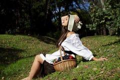 一件白色女衬衫的,在自然的一个帽子美丽的女孩 免版税库存照片