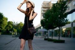 一件白色帽子和黑礼服的年轻美丽的妇女走沿一条街道的在一个城市在夏天 库存照片