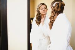 一件白色晨衣的女孩在镜子看 免版税库存照片