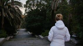 一件白色温暖的夹克的年轻白肤金发的妇女在公园进来楼下 后方后面视图 影视素材