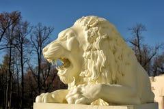一头白色狮子的雕塑在蓝天背景的  免版税库存照片
