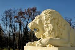 一头白色狮子的雕塑在蓝天背景的  免版税库存图片
