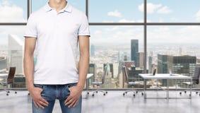 一件白色球衣和牛仔布的一个人握他的在口袋的手 一个现代全景办公室空间在纽约 免版税库存图片