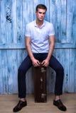 一件白色球衣的高英俊的人坐老褐色 免版税库存照片