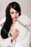 一件白色皮大衣的美丽的女孩 免版税库存照片