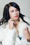 一件白色皮大衣的美丽的女孩 免版税库存图片