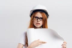 一件白色盔甲的年轻美丽的妇女在轻的背景拿着一张图画,情感,画象,工程师 免版税图库摄影