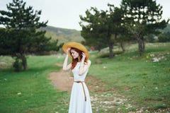 一件白色礼服和戴的一个帽子年轻美丽的妇女在山 库存照片