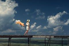 一件白色礼服的一个女孩沿一个木桥走 马尔代夫 印度洋 库存照片