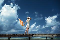 一件白色礼服的一个女孩沿一个木桥走 马尔代夫 印度洋 库存图片