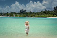 一件白色礼服的一个女孩进入水 马尔代夫 海滩 印度洋 免版税库存图片