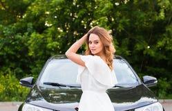 一件白色礼服的一个少妇有室外一辆黑的汽车的 免版税库存照片