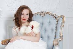 一件白色礼服的一个深色头发的女孩在一把深扶手椅子坐并且拿着玩具熊 免版税库存图片