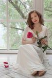 一件白色礼服的一个美丽的女孩坐与她的地板回到窗口 她离开了她的鞋子并且举行了a 库存图片