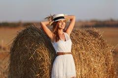 一件白色礼服的一个美丽的苗条女孩在干草附近站立 免版税库存照片