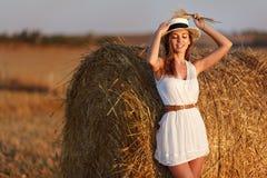 一件白色礼服的一个美丽的苗条女孩在干草附近站立 库存图片