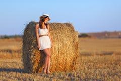 一件白色礼服的一个美丽的苗条女孩在干草附近站立 库存照片