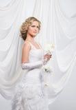 一件白色礼服的一个年轻和可爱的白肤金发的新娘 免版税库存图片